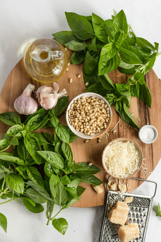 Ingredients for pesto on wooden cutting board.