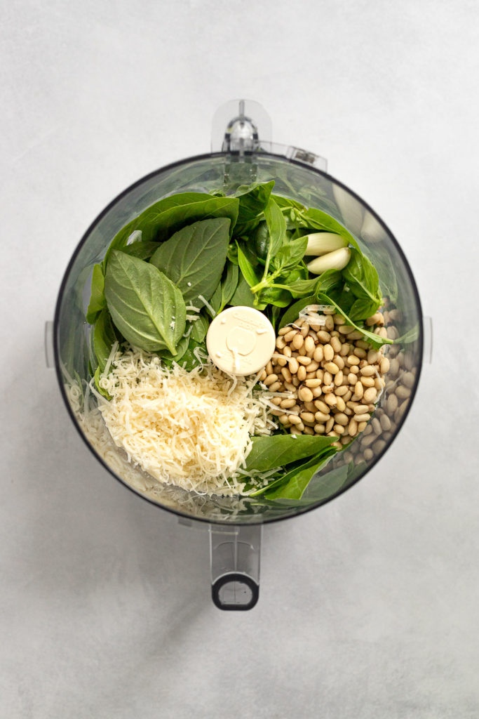 Basil, cheese, garlic, and pine nuts in food processor.