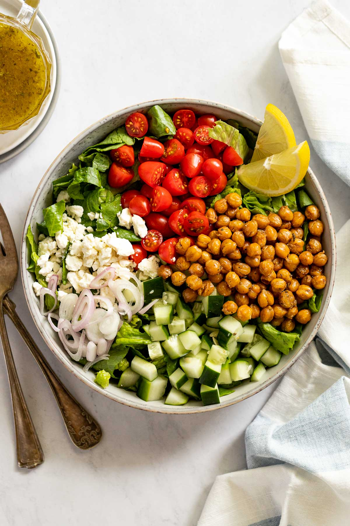 Shallot, feta, tomatoes, chickpeas, and cucumber on bed of lettuce in a bowl.