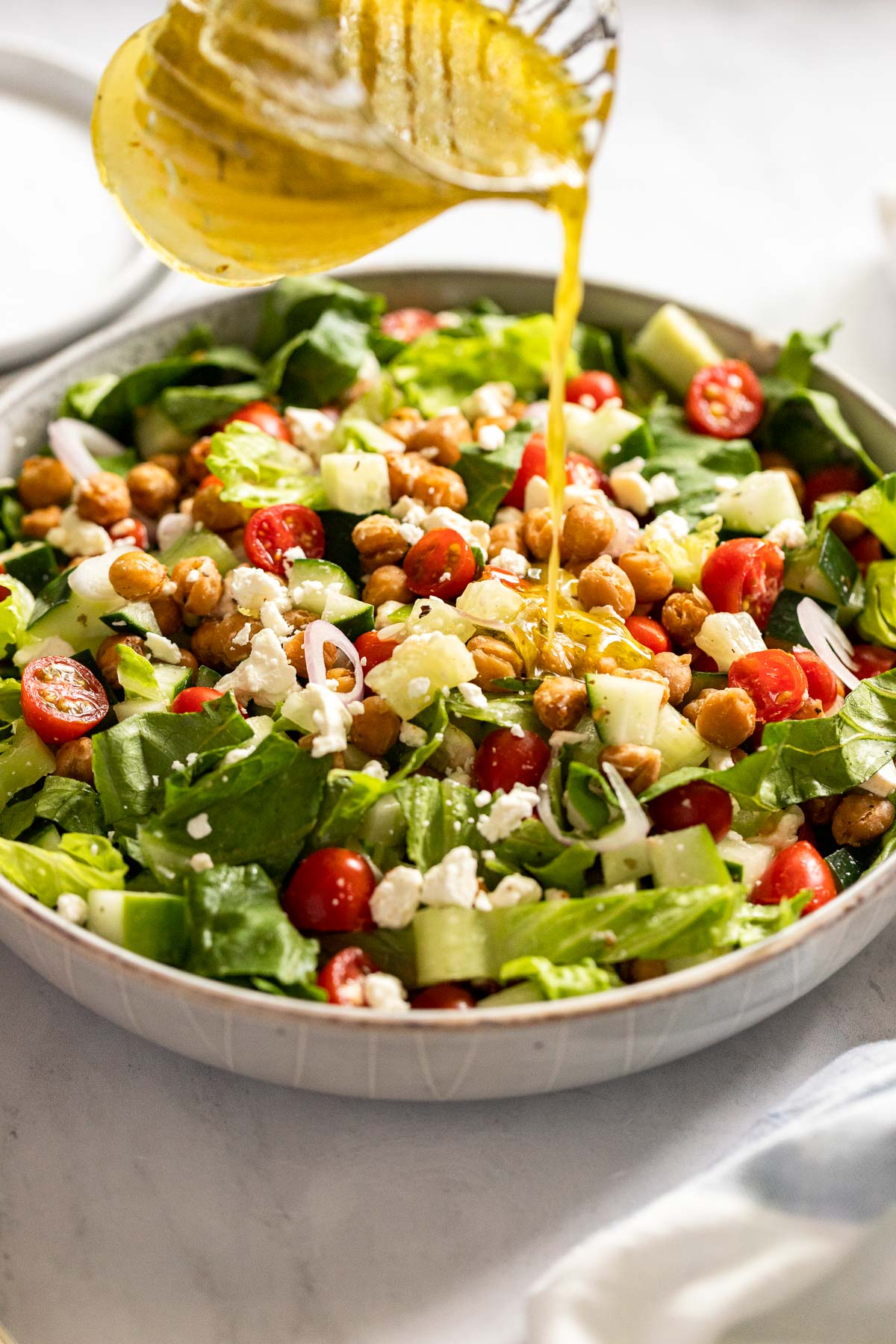 Pouring dressing onto salad in a bowl.