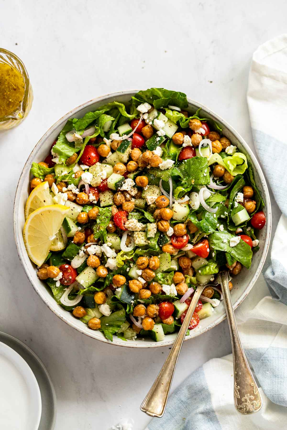 Bowl of salad with spoon and fork sticking out of it next to a linen.