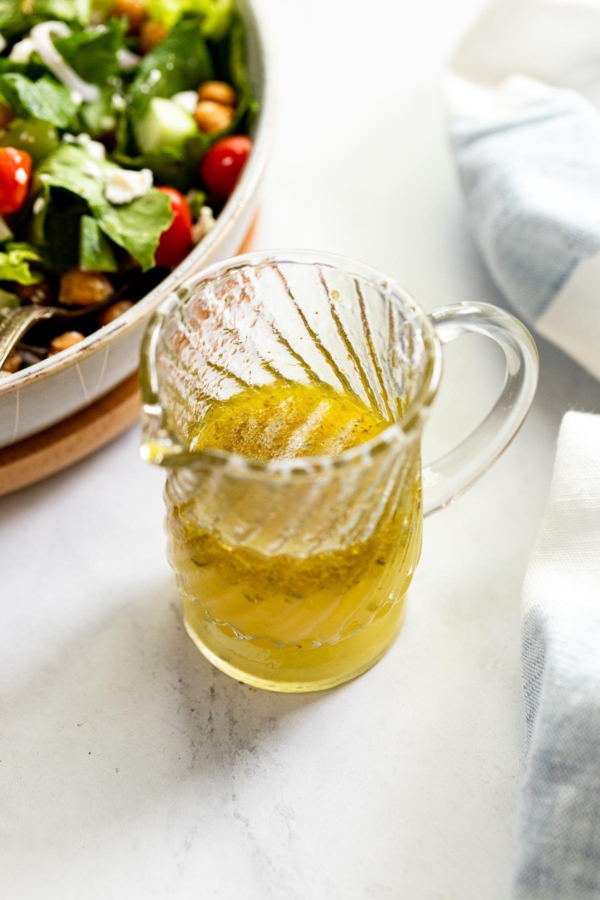 Jar of dressing next to a salad.