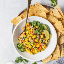 bowl of pineapple salsa on a tray with jalapenos and cilantro with spoon