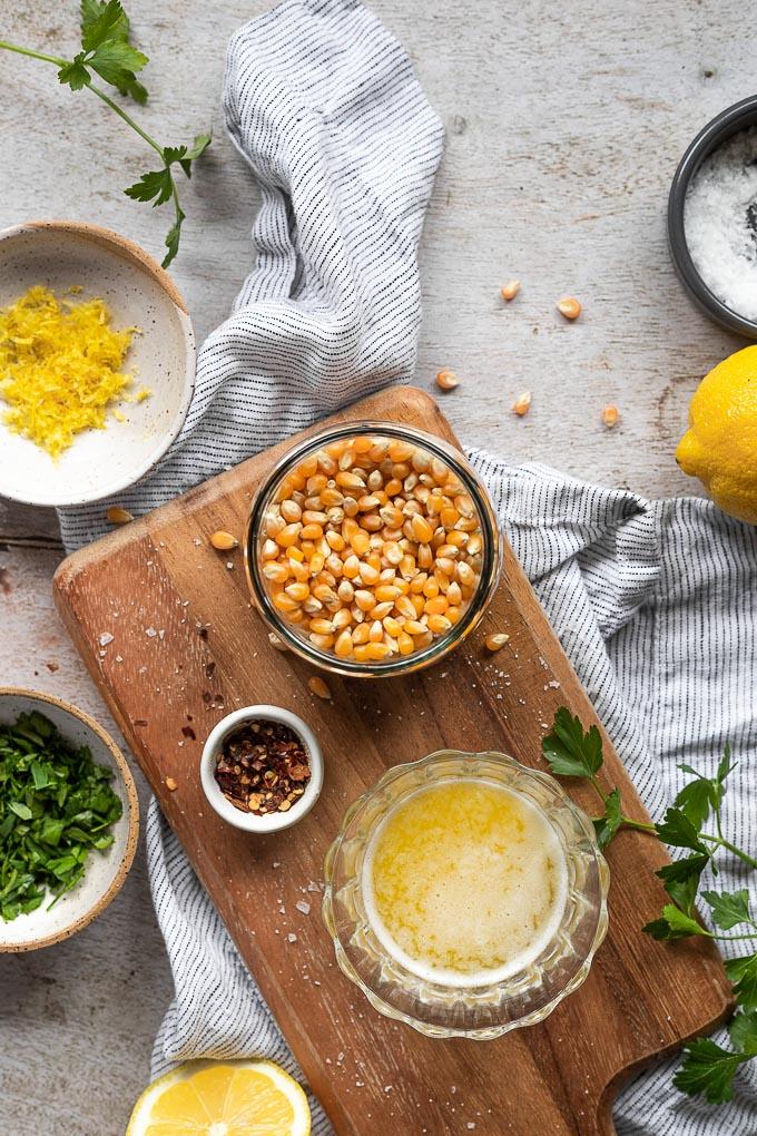 Ingredients for lemon parsley popcorn on wood board.