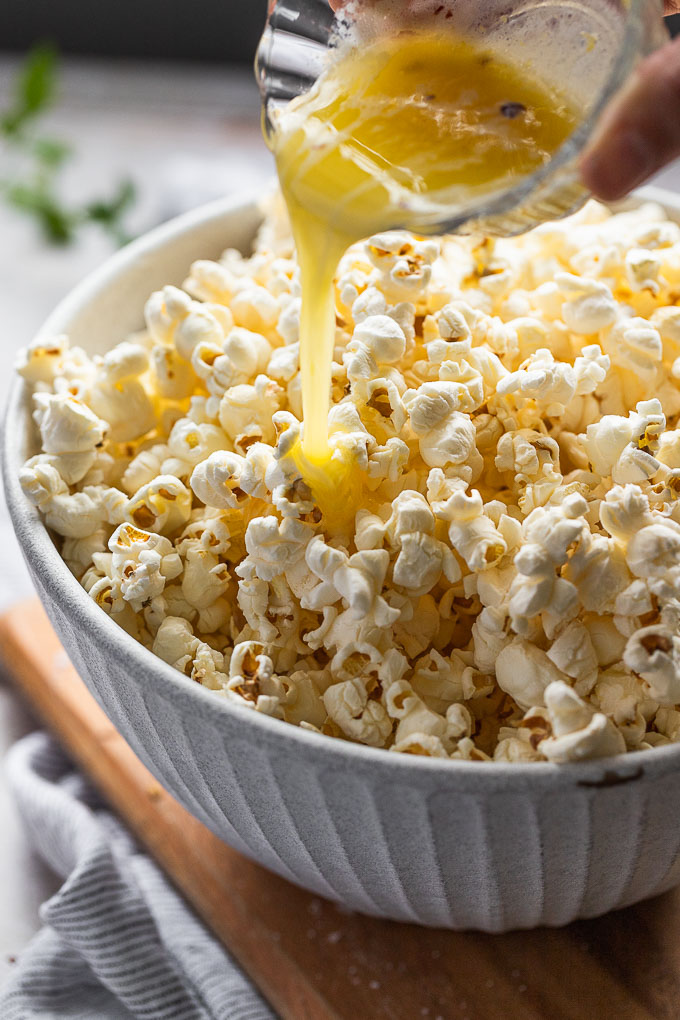 Pouring melted butter into bowl of popcorn.