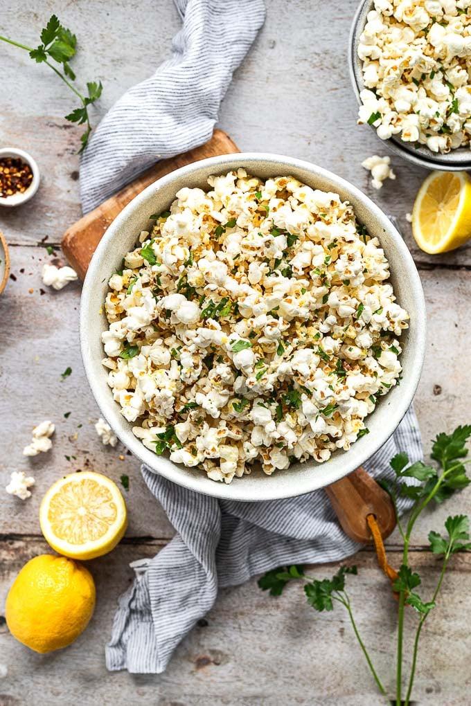 Big bowl of lemon popcorn next to smaller bowl and parsley.