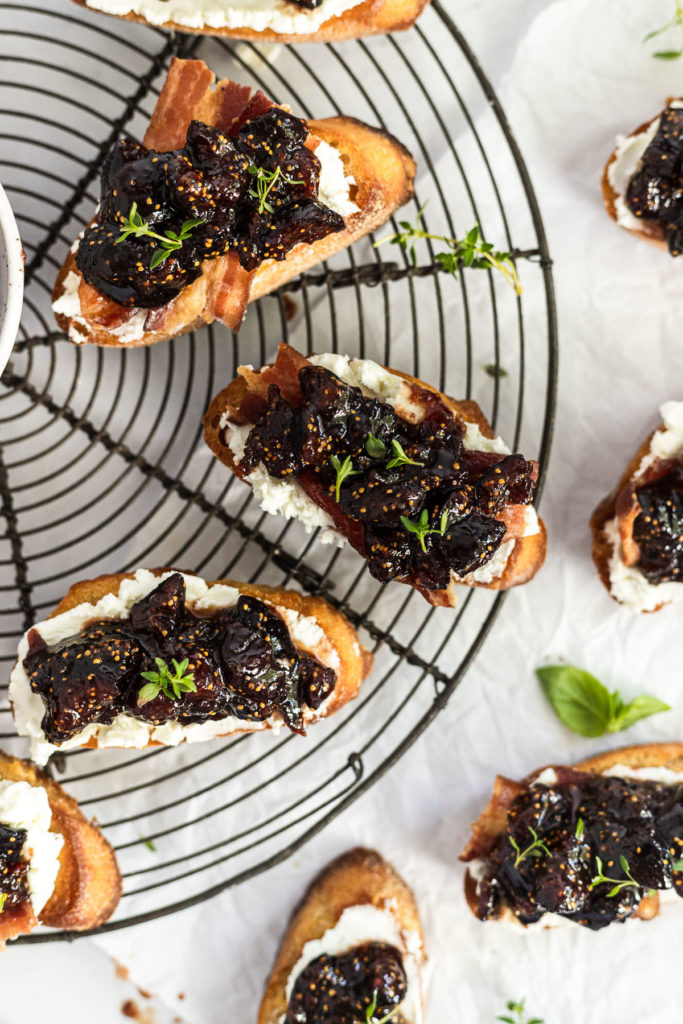 Fig and goat cheese crostini on wire rack.