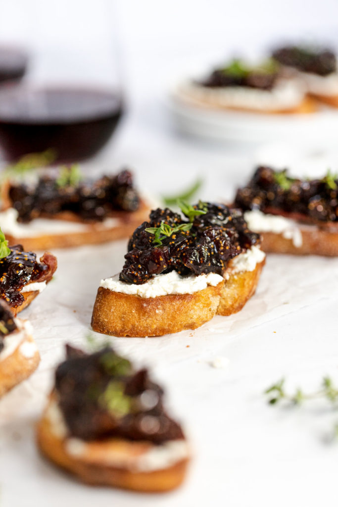 Fig compote and goat cheese crostini next to wine glasses.