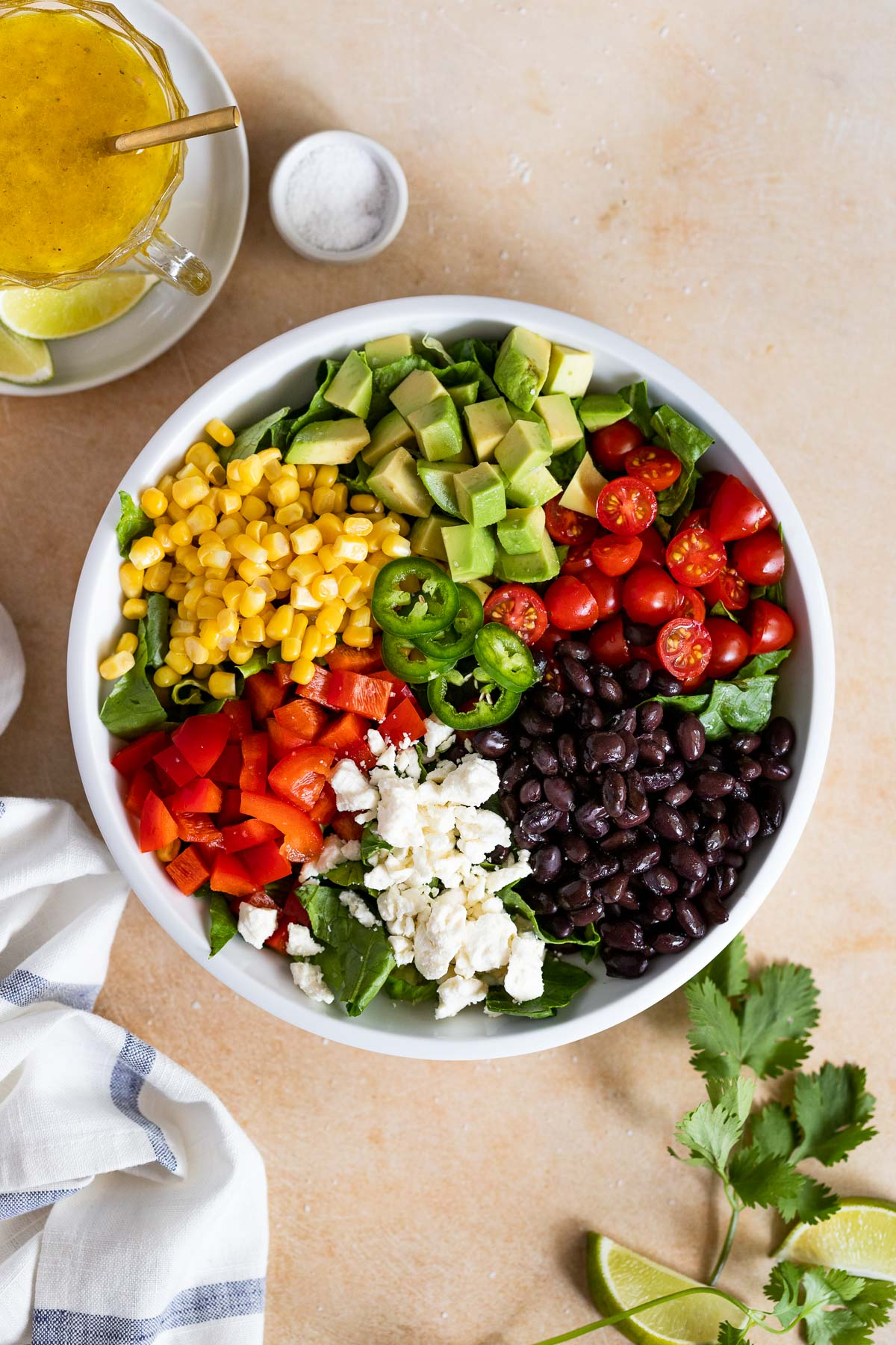 Corn, avocado, red bell pepper, tomato, black beans, and feta on top of romaine lettuce in a bowl.