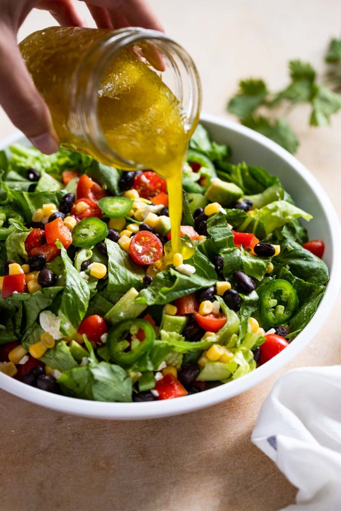 Pouring dressing on salad.