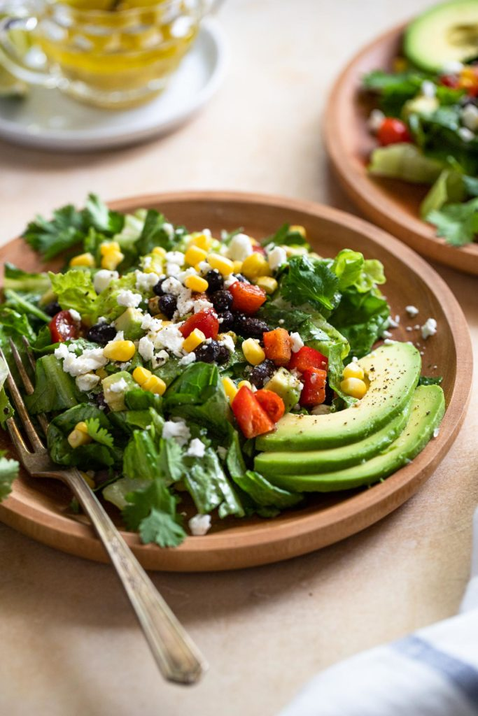 Side view of wood plate with salad and fork.