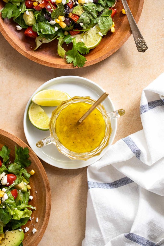 Honey Lime Dressing on white plate next to salads.