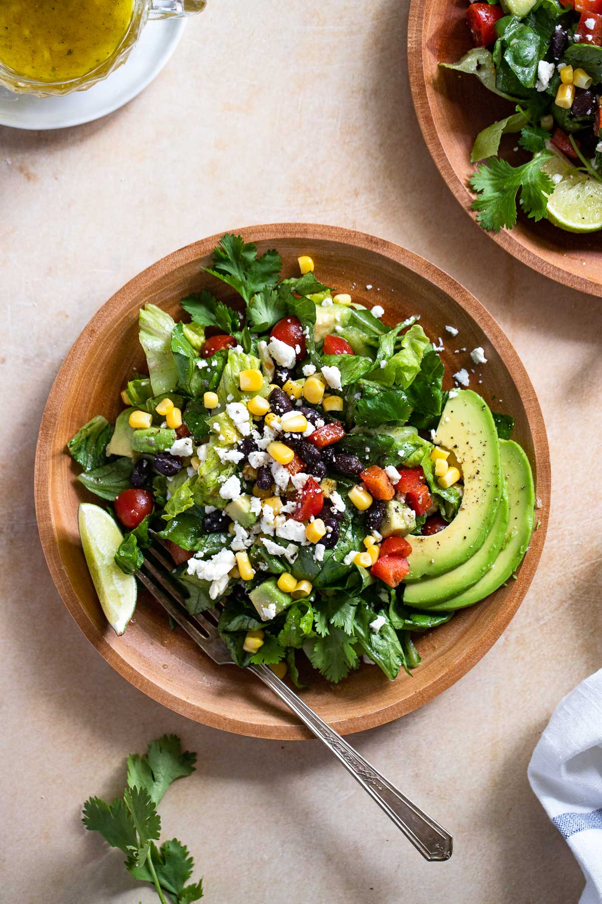 Southwest salad on wooden plate with fork.