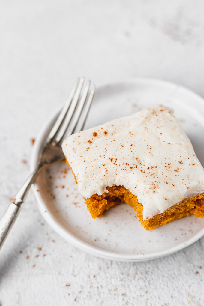 Pumpkin bar with bite taken out of it on a plate.