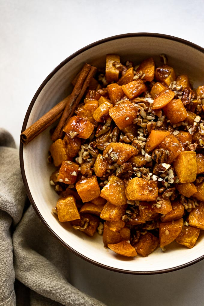 Up close tan bowl with roasted butternut squash, cinnamon sticks, and pecans.