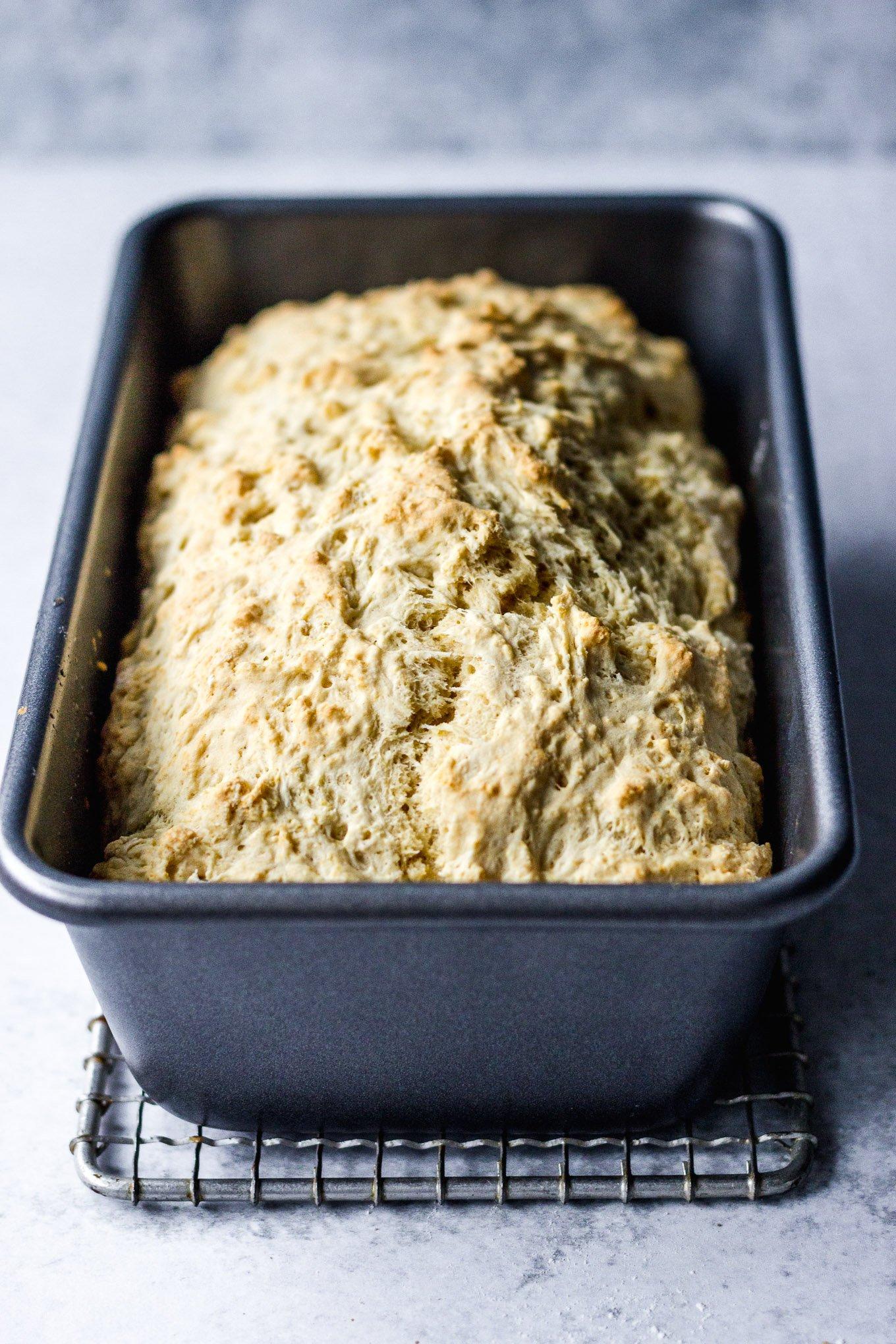 beer bread in baking loaf pan on cooling rack
