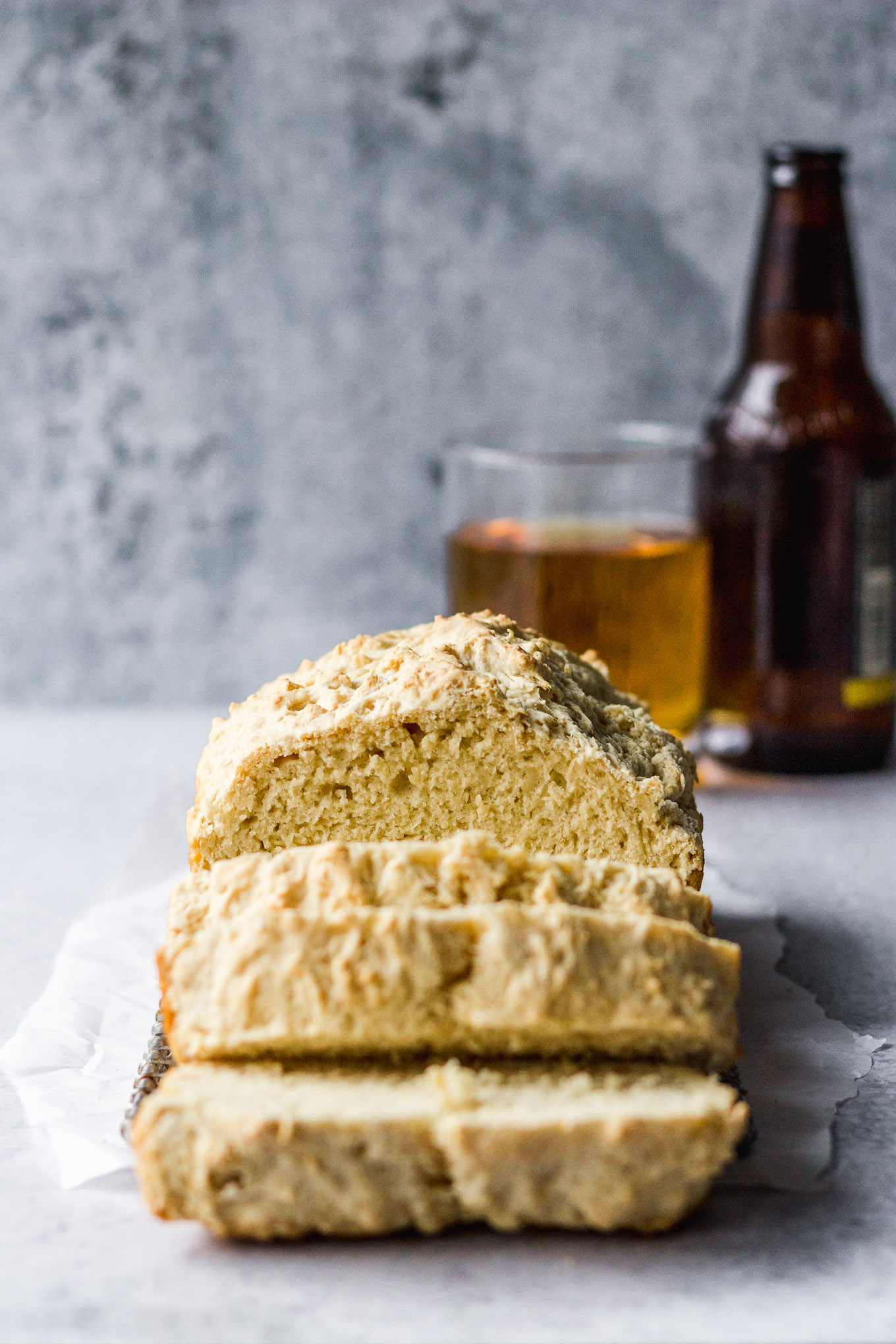 beer bread loaf sliced with beer in the background