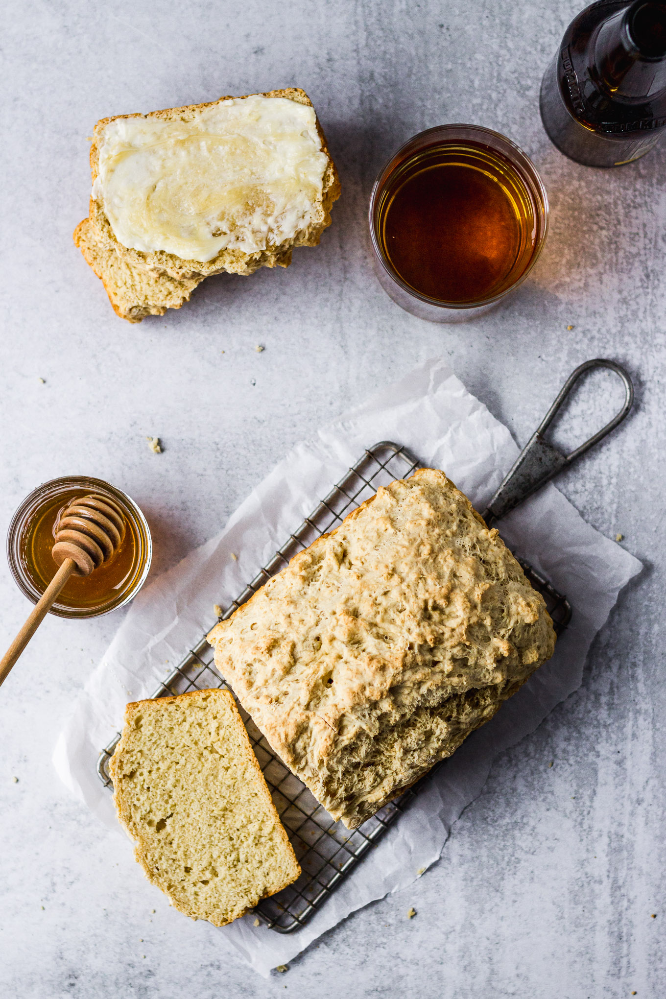 beer bread loaf sliced next to beer and honey jar with butter spread on a slice