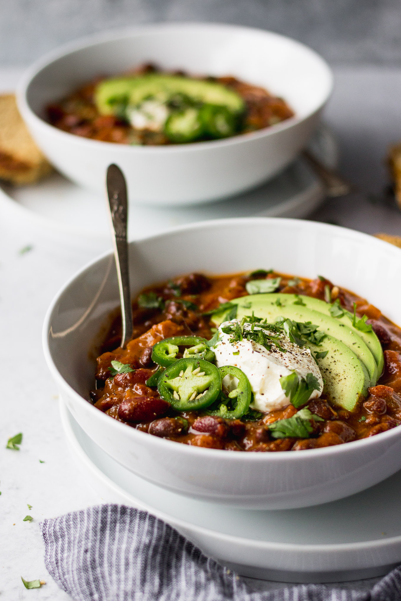 spicy vegetarian bean chili with avocado, jalapeno, and sour cream in white bowl with bread by fork in the kitchen