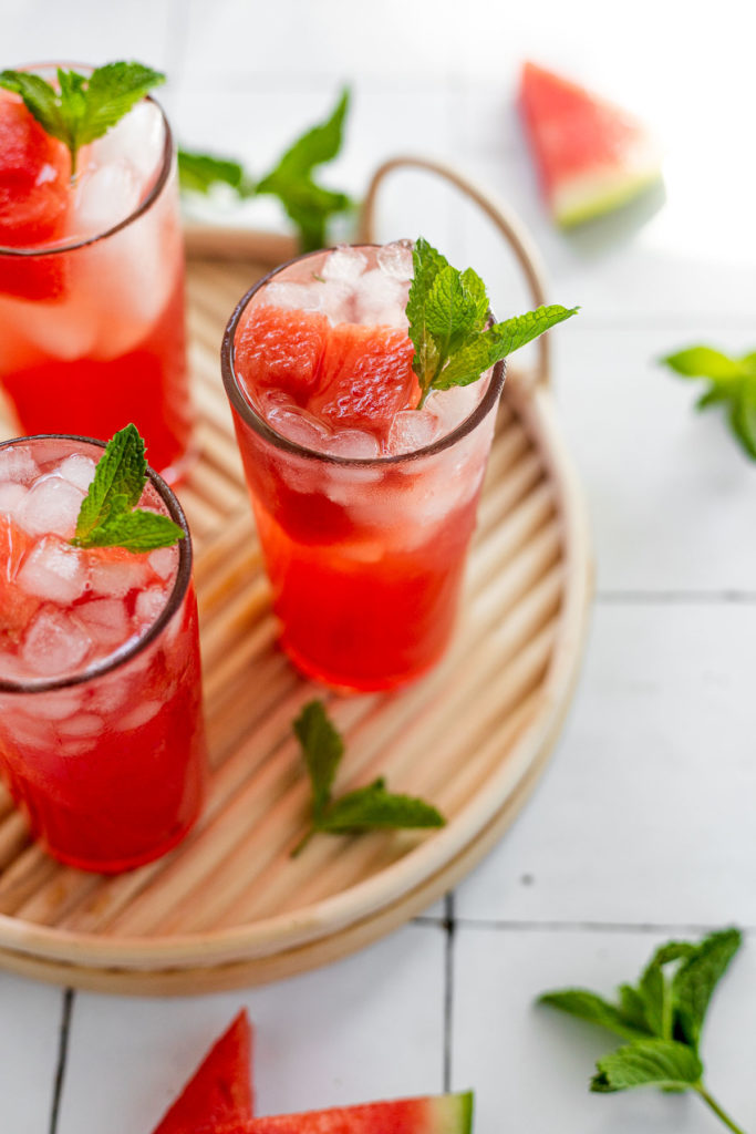 Three glasses of watermelon mint cocktail on wood serving tray.