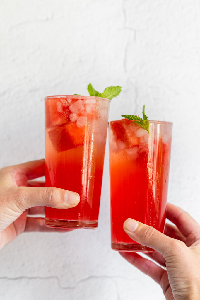 Two watermelon cocktails cheersing.