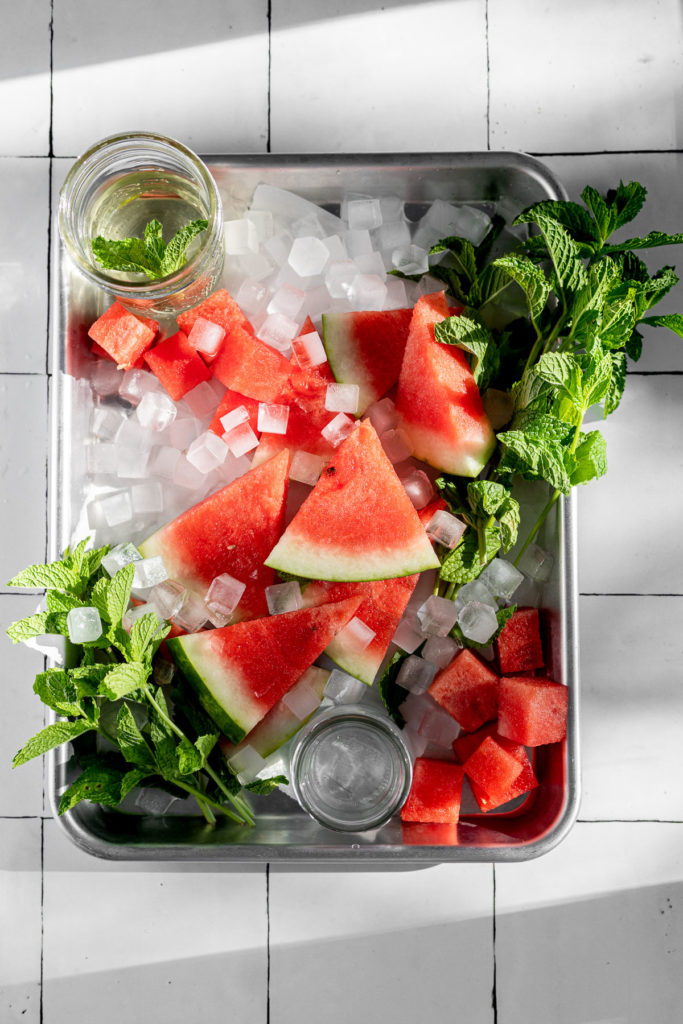 Serving tray with ice, watermelon slices, mint, and vodka.