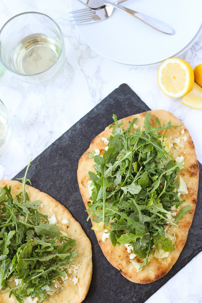 overhead view of two naan flatbread topped with artichokes and arugula on black slate next to white plates