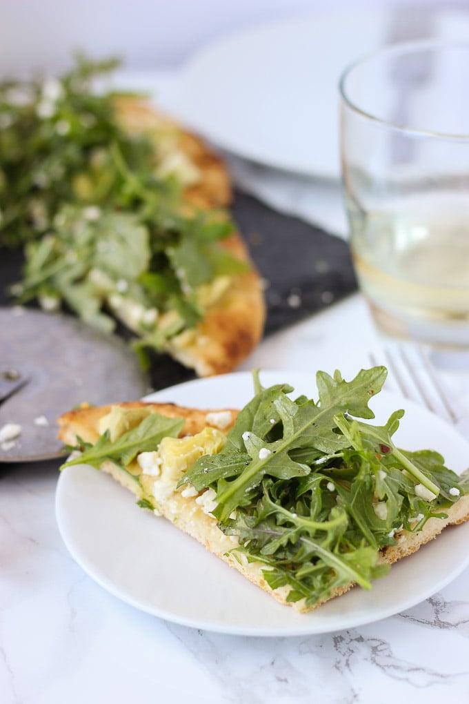 slice of Artichoke and Arugula Flatbread on white plate