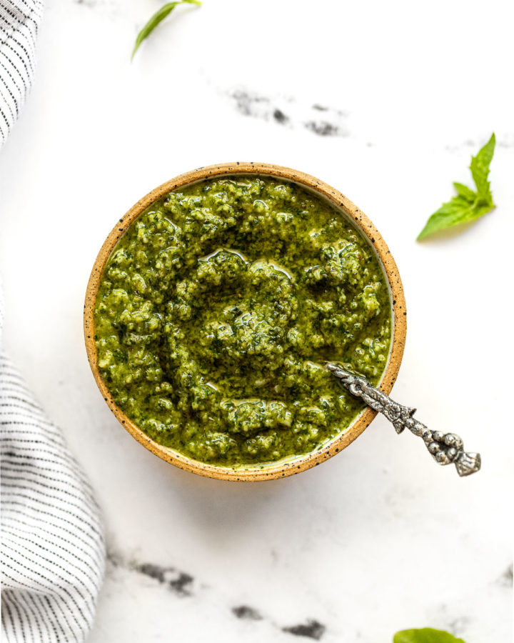 Small bowl with basil mint pesto and spoon.
