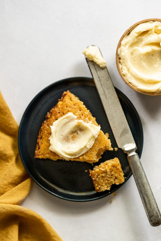 Cornbread slice with butter spread on top next to knife.
