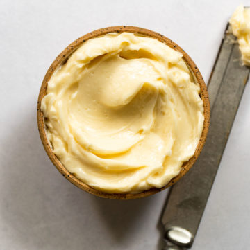 Bowl of whipped honey butter next to knife.