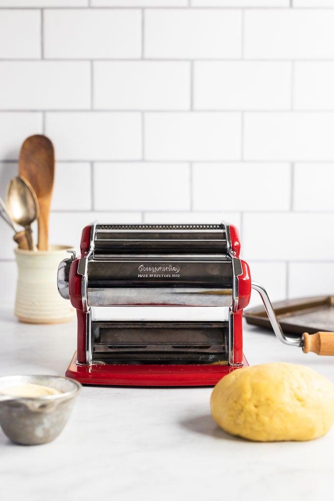 Red pasta machine next to pasta dough ball, flour, and baking sheet.