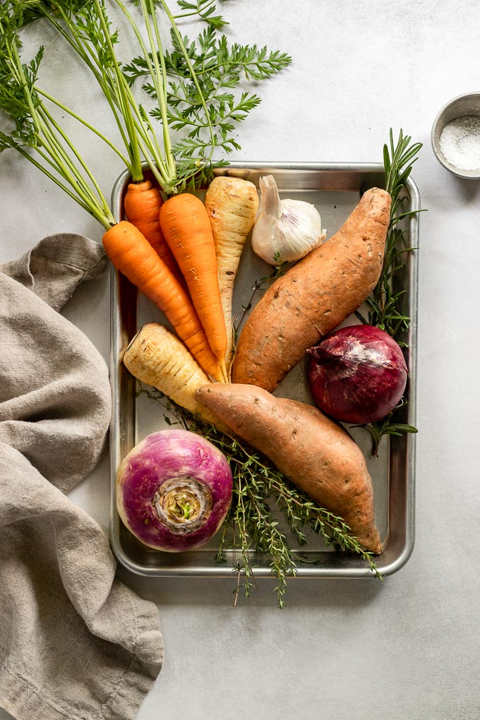 Tray with carrots, garlic, sweet potato, onion, herbs, and turnip.