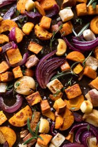 Baking sheet with roasted root vegetables: onion, garlic, sweet potato, carrot, parsnip.