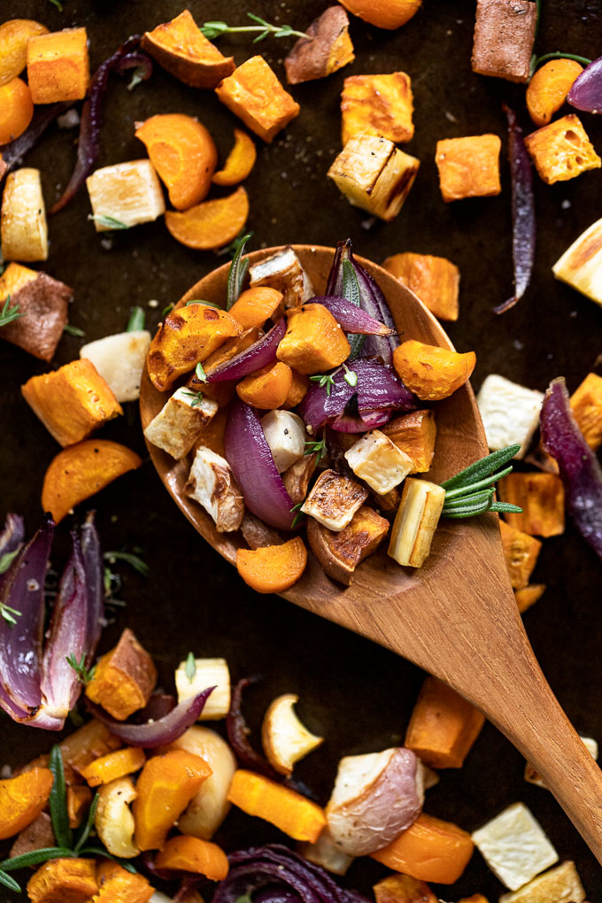 Spoon of roasted vegetables surrounded by others on a baking tray.
