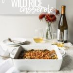 green bean rice casserole in white baking dish next to linen in front of red flowers, wine glasses, and wine bottle