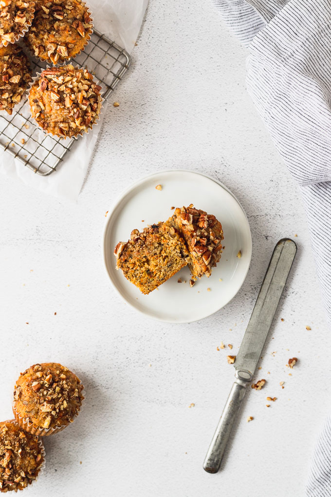 overhead banana carrot muffins on white plate and cooling rack next to knife
