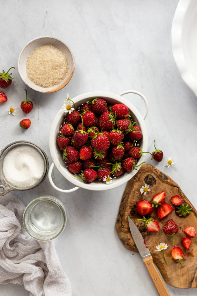 Ingredients for fresh strawberry pie in bowls by each other.