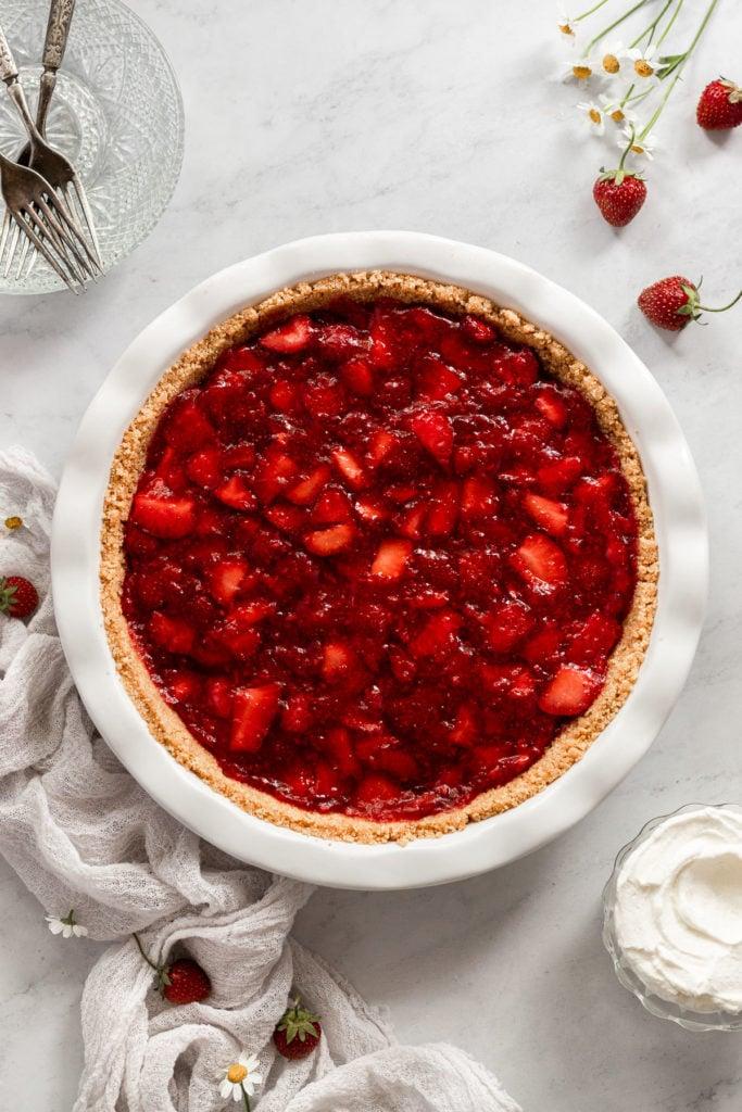 Strawberry pie in pie plate next to linen.