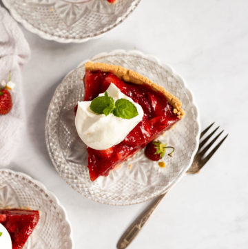 Overhead strawberry pie slice next to two other plates and a fork.