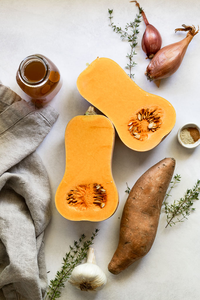 Butternut squash cut in half next to sweet potato, stock, garlic, thyme, and shallot.
