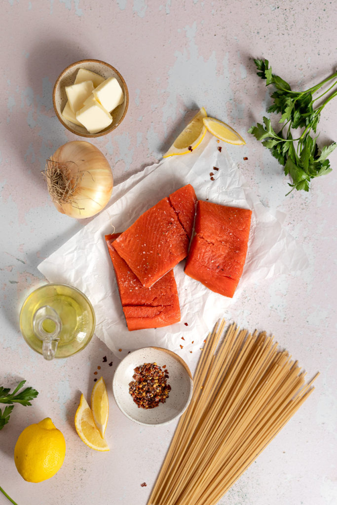 Salmon filets, spaghetti pasta, lemon, olive oil, onion, and parsley laid out on table.