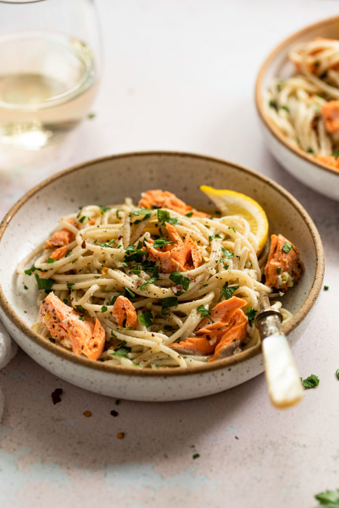 Side view of white bowl with salmon garlic butter pasta with fork.