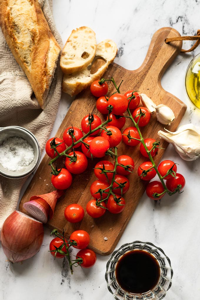 Cutting board with cherry tomatoes, baguette, shallot, garlic, and balsamic vinegar.
