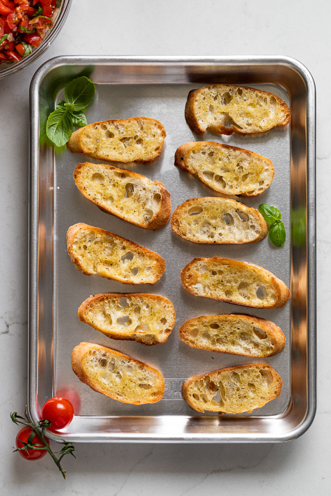 Crostini on baking sheet next to bowl of tomato mixture.