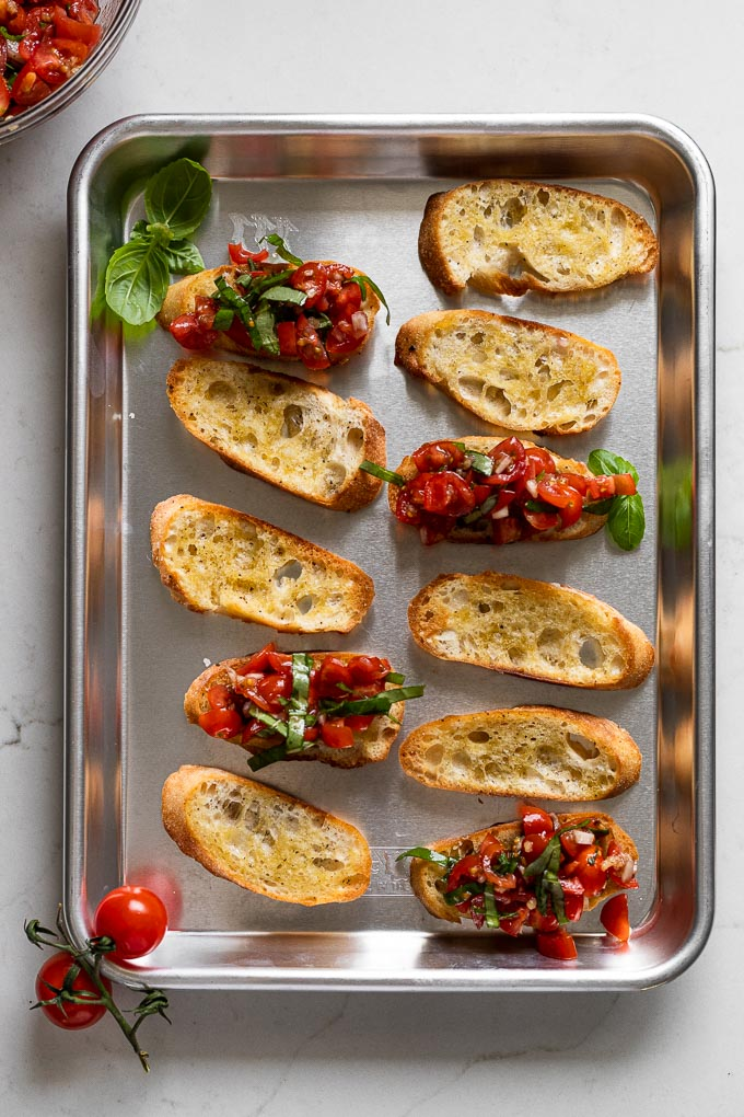 Crostini on baking sheet, some topped with bruschetta mixture.
