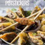 potsticker on top of ponzu sauce with chopsticks