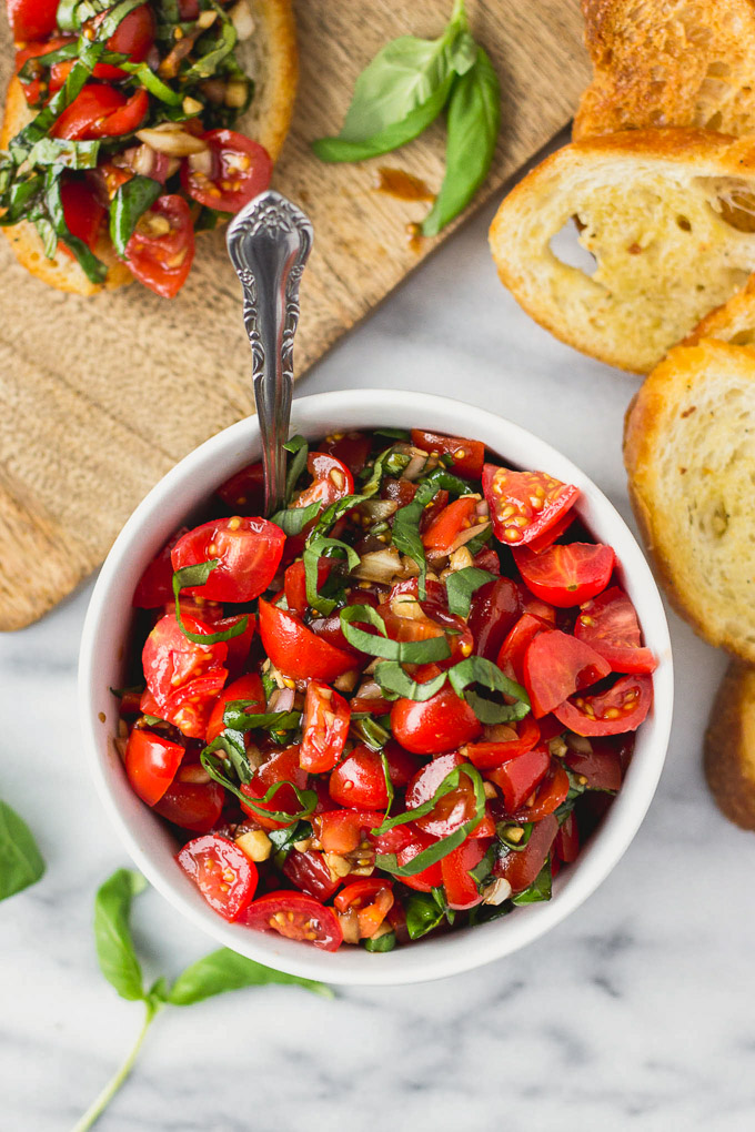 Bowl of diced tomatoes, basil, garlic, and balsamic tossed together.