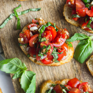Overhead looking at bruschetta on cutting board next to basil leaves.