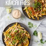 overhead of two plates with french fries topped with cheese, kimchi, sauce, and green onions